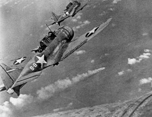 Two American SBD's fly over a Japanese ship, presumably Mikuma, during the Battle of Midway.